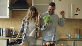 Het aantrekkelijke jonge blije paar heeft en pret die terwijl thuis het koken in de keuken dansen zingen stock video