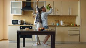 Het aantrekkelijke jonge blije paar heeft en pret die terwijl thuis het koken in de keuken dansen zingen stock foto's