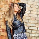 Het aantrekkelijke jonge blondevrouw stellen door de muur Royalty-vrije Stock Fotografie