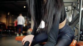 Het aantrekkelijke jonge Kaukasische meisje die bicepsen doen oefent terwijl het zitten op de bank en het opheffen van domoor in  stock footage
