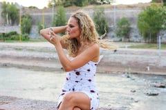 Het aantrekkelijke Jonge Meisje die met Krullend Blond Haar haar controleren maakt omhoog royalty-vrije stock fotografie