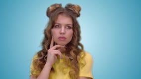 Het aantrekkelijke jonge meisje in een gele T-shirt denkt na Close-up stock video