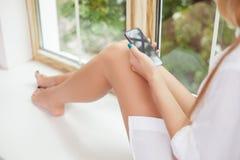 Het aantrekkelijke jonge meisje ontspant dichtbij een venster Royalty-vrije Stock Afbeeldingen