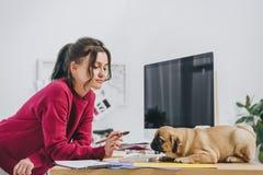 Het aantrekkelijke jonge meisje spelen met pug terwijl het werken aan illustraties royalty-vrije stock foto's
