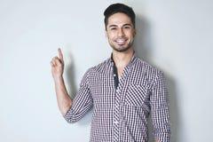 Het aantrekkelijke jonge mens gesturing met wijsvinger aan de muur Royalty-vrije Stock Afbeeldingen