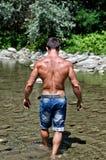 Het aantrekkelijke jonge muscleman die lopen in watervijver van de rug wordt gezien Stock Foto's
