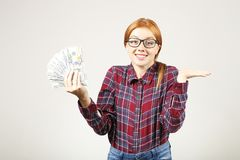 Het aantrekkelijke jonge onderneemster stellen met bos van USD-contant geld in handen die positieve emoties en gelukkige gelaatsu stock afbeelding