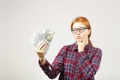 Het aantrekkelijke jonge onderneemster stellen met bos van USD-contant geld in handen die positieve emoties en gelukkige gelaatsu Royalty-vrije Stock Foto