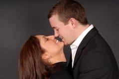 Het aantrekkelijke jonge paar in elke anderen bewapent het staren bij elke othe Stock Afbeelding