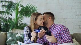 Het aantrekkelijke jonge paar met smartphone en de creditcard die op Internet winkelen zitten thuis op laag in woonkamer royalty-vrije stock foto's