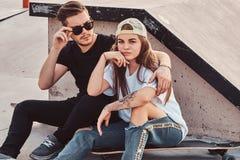 Het aantrekkelijke jonge paar zit bij zonnige skatepark met hun longboards naast de helling stock foto's