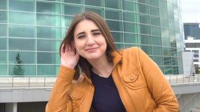 Het aantrekkelijke jonge vrouw afluisteren openlucht in de stad in winderige dag stock footage