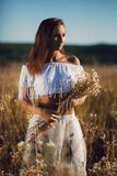 Het aantrekkelijke jonge vrouw bevindende stellen op het gebied van lang gras op zonsondergang stock afbeeldingen