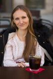 Het aantrekkelijke jonge vrouw glimlachen die zich bij een terras bevinden Stock Afbeeldingen