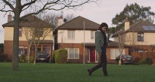 Het aantrekkelijke jonge vrouw lopen door het gras in het landgoed, kijkt zij aan de camera en pensively gaat zij, binnen door stock footage
