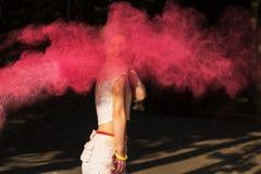 Het aantrekkelijke jonge vrouw spelen met roze droge verf Holi explodin Royalty-vrije Stock Afbeelding