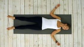 Het aantrekkelijke jonge vrouw thuis uitwerken, doend yogaoefening, die in Shavasana-Lijk of Lijk liggen stelt, het rusten royalty-vrije stock afbeelding