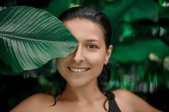 Het aantrekkelijke Kaukasische donkerbruin meisje model stellen in een pool met groene installaties Schoonheidsmiddelen reclame royalty-vrije stock fotografie