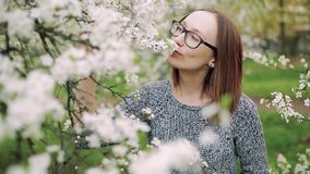 Het aantrekkelijke Kaukasische meisje in glazen geniet van geur van witte tot bloei komende kers Het schot van de close-up stock videobeelden