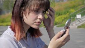 Het aantrekkelijke Kaukasische Vrouw Gladstrijken en maakt Haar Haar recht Kijkend in Spiegel stock footage