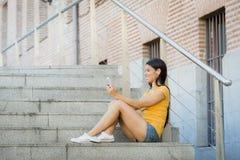 Het aantrekkelijke Latijnse vrouw texting op haar slimme telefoon royalty-vrije stock afbeelding