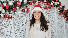 Het aantrekkelijke leuke meisje met het verbazende glimlach kussen die de camera op Kerstmis bekijken verfraaide achtergrond stock videobeelden