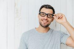 Het aantrekkelijke mannelijke model met stoppelveld, kijkt vreugdevol door spect stock foto's