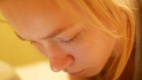 Het aantrekkelijke meisje die van de blonde Kaukasische tiener op een bed vallen thuis en op haar telefoon texting stock videobeelden