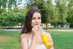 Het aantrekkelijke meisje drinkt in openlucht vers sap door het stro De mooie vrouw houdt een fles koude limonade stock foto