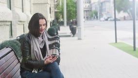 Het aantrekkelijke meisje in een leer zwart jasje en een grijze sjaal zit op een bank en bekijkt de telefoon Hij heft zijn hoofd  stock footage