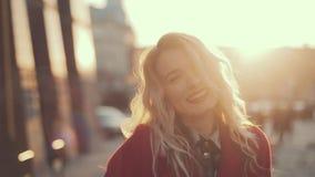 Het aantrekkelijke meisje in een rode laag gaat onderaan de straat in een stad, glanst de zon, dan draaien aan camera en glimlach stock videobeelden