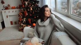 Het aantrekkelijke meisje in een warme sweater zit dichtbij de Kerstboomglimlachen en kijkt uit het venster stock video
