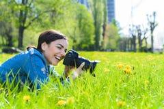 Het aantrekkelijke meisje in een weide neemt beelden van bloemen Royalty-vrije Stock Fotografie