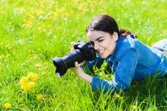Het aantrekkelijke meisje in een weide neemt beelden van bloemen Royalty-vrije Stock Afbeeldingen