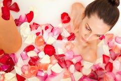 Het aantrekkelijke meisje geniet van een bad met melk en rozen Royalty-vrije Stock Afbeelding