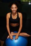 Het aantrekkelijke meisje met een mooie glimlach is bezet met fitball royalty-vrije stock fotografie
