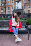 Het aantrekkelijke meisje met lang haar zit op een bank, die in een rode deken, in een nieuw woonkwart wordt behandeld en schrijf Stock Afbeelding