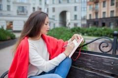 Het aantrekkelijke meisje met lang haar zit op een bank, die in een rode deken, in een nieuw woonkwart wordt behandeld en schrijf Royalty-vrije Stock Afbeeldingen