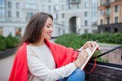 Het aantrekkelijke meisje met lang haar zit op een bank, die in een rode deken, in een nieuw woonkwart wordt behandeld en schrijf stock fotografie