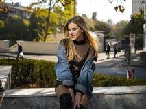 Het aantrekkelijke meisje met mooi stromend haar zit op een bank op een mooie zonnige dag royalty-vrije stock fotografie