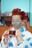 Het aantrekkelijke meisje met rood haar met een van het kleimasker en haar krulspelden in haarkosten in keuken in een peignoir en Royalty-vrije Stock Fotografie