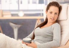 Het aantrekkelijke meisje ontspannen in leunstoel thuis Stock Afbeeldingen