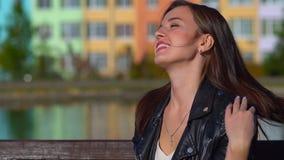 Het aantrekkelijke meisje op de straat in het Park, maakt haar haar, het glimlachen recht stock footage