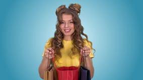 Het aantrekkelijke meisje opent pakketten en geniet van winkelend na het winkelen stock videobeelden