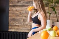 Het aantrekkelijke meisje in sportkleding bereidt een gezond ontbijt v??r de training in de keuken voor, snijdt fruit en dranken stock afbeeldingen