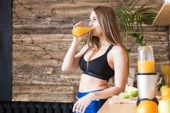 Het aantrekkelijke meisje in sportkleding bereidt een gezond ontbijt v??r de training in de keuken voor, snijdt fruit en dranken royalty-vrije stock afbeelding