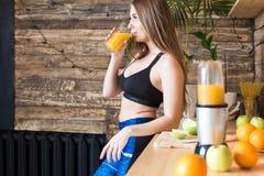 Het aantrekkelijke meisje in sportkleding bereidt een gezond ontbijt v??r de training in de keuken voor, snijdt fruit en dranken stock foto