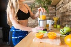 Het aantrekkelijke meisje in sportkleding kookt in de keuken een gezonde drank na een training en het drinken vers binnen gemaakt stock foto
