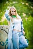 Het aantrekkelijke meisje stellen in jeans openlucht Stock Afbeeldingen