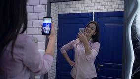 Het aantrekkelijke meisje stellen voor spiegel voor selfiefoto op celtelefoon in toilet stock footage
